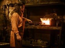Старший кузнец нагревает деталь перед ковать в кузнице стоковые фото