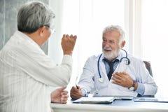 Старший мужской доктор и азиатский мужской пациент говорят стоковое изображение