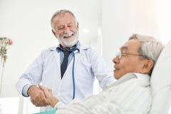 Старший мужской доктор разговаривает с азиатским мужским пациентом стоковая фотография rf