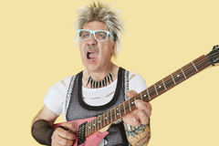 Старший мужской панковский музыкант играя гитару над желтой предпосылкой Стоковая Фотография