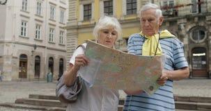 Старший мужчина и женские туристы идя с картой в руках ища маршрут сток-видео
