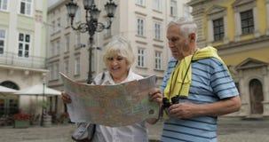 Старший мужчина и женские туристы идя с картой в руках ища маршрут акции видеоматериалы
