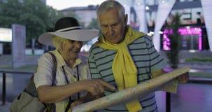 Старший мужчина и женские туристы стоя с картой в руках ища маршрут видеоматериал