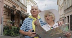 Старший мужчина и женские туристы стоя с картой в руках ища маршрут акции видеоматериалы