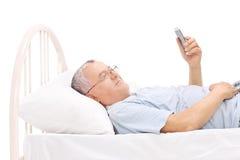 Старший наблюдая что-то на его сотовом телефоне в кровати Стоковое Изображение RF