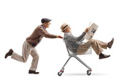 Старший нажимая магазинную тележкау с другим старшием с newspa стоковые фотографии rf