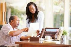 Старший отец обсуждая документ с взрослой дочерью стоковая фотография rf