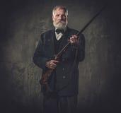 Старший охотник с корокоствольным оружием в традиционной одежде стрельбы, представляя на темной предпосылке Стоковые Изображения RF