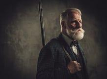 Старший охотник с корокоствольным оружием в традиционной одежде стрельбы, представляя на темной предпосылке Стоковые Фотографии RF