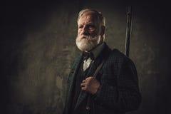 Старший охотник с корокоствольным оружием в традиционной одежде стрельбы, представляя на темной предпосылке Стоковые Фото