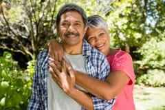 Старший один другого обнимать пар в саде на солнечный день Стоковое Фото