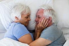 Старший один другого обнимать пар в спальне Стоковые Изображения