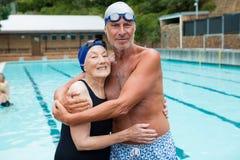 Старший один другого обнимать пар на poolside Стоковая Фотография