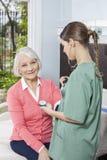 Старший пациент получая ей кровяное давление проверенный женским Nurs Стоковое Изображение