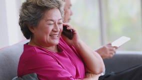 Старший планшет пользы пар и говорить к мобильному телефону сток-видео