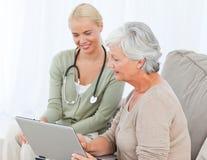 Старший при ее доктор работая на компьтер-книжке стоковое изображение rf