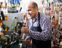 Старший профессионал с разными видами ключей в locksmith стоковая фотография rf