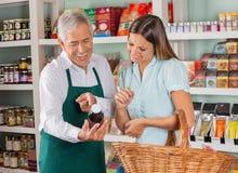 Старший продавец помогая женскому клиенту внутри Стоковое Изображение RF