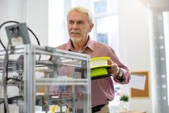 Старший работник офиса быть около ввести нить в принтер стоковые фото