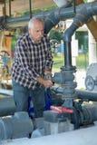 Старший работник поворачивает клапан обхода на станции компрессора газа Стоковое Изображение