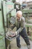 Старший работник сверлит скважины на детали бурильщиком Стоковые Изображения