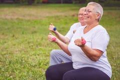 Старший резвится женщина сидя на шарике фитнеса с гантелями Стоковые Фото