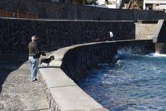 Старший рыболов и его рыбная ловля собаки на пристани Стоковое Изображение RF