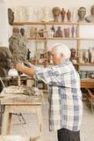 Старший скульптор делая взгляд профиля скульптуры стоковое изображение