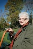 старший стенда сидит женщина Стоковое Фото