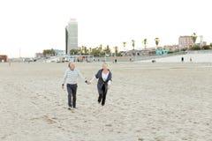 Старший счастливые супруг и жена бежать на пляже песка и держа руки стоковая фотография rf