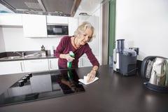 Старший счетчик кухни чистки женщины стоковое изображение rf