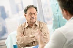 Старший терпеливейший слушать к доктору стоковое фото rf