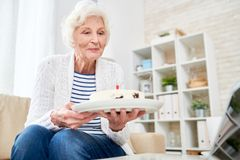 Старший торт показа женщины через компьтер-книжку app стоковое фото rf
