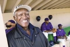 Старший тренер усмехаясь с игроками в предпосылке Стоковое Изображение RF