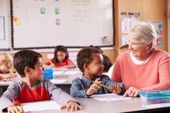 Старший учитель сидя с начальной школой ягнится в классе Стоковое Изображение RF