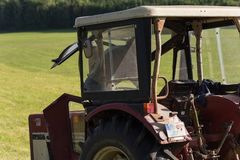 старший фермер haying с старым трактором стоковая фотография rf