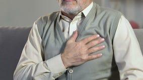 Старший человек внезапно чувствуя боль в комоде, кардиологическую проблему, сердечный приступ видеоматериал