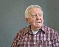 Старший человек восьмидесятилетнего старика в шотландке с серой предпосылкой стоковое изображение