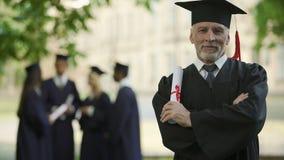 Старший человек в академичной регалии держа диплом, образование на любом времени, новую степень акции видеоматериалы