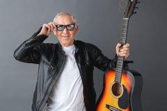 Старший человек в кожаной куртке и солнечных очках стоя на серой держа гитаре касаясь стеклам крутым стоковые фотографии rf