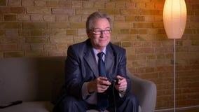 Старший человек в костюме играя видеоигру с кнюппелем по телевизору быть ликующий и радостный дома сток-видео
