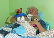 Старший человек в кровати с мягкими привлекательными игрушками стоковое фото rf