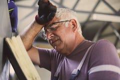 Старший человек в мастерской Потревоженный человек читая его плановика Стоковые Фото