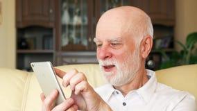 Старший человек дома используя мобильный телефон, просматривающ, читающ новости Через активную современную жизнь после выхода на  акции видеоматериалы