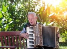 Старший человек играя аккордеон стоковая фотография