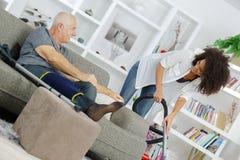 Старший человек идя используя костыли на софе говоря к ассистенту стоковое изображение rf