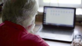 Старший человек используя компьтер-книжку сидя на таблице дома видеоматериал