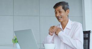 Старший человек используя ноутбук и возбужденный о нем видеоматериал
