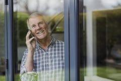 Старший человек используя телефон на окне Стоковое Изображение