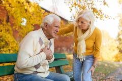 Старший человек испытывая боль в груди пока старшая женщина утешает его стоковое изображение rf